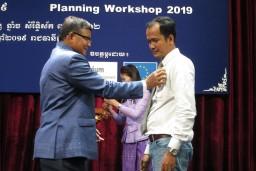 Virak Uon, programmacoördinator Klassenmanagement, ontvangt zijn medaille van de minister