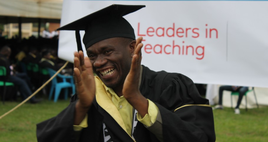 Happy graduate in front of Mastercard Foundation's Leaders in Teaching logo